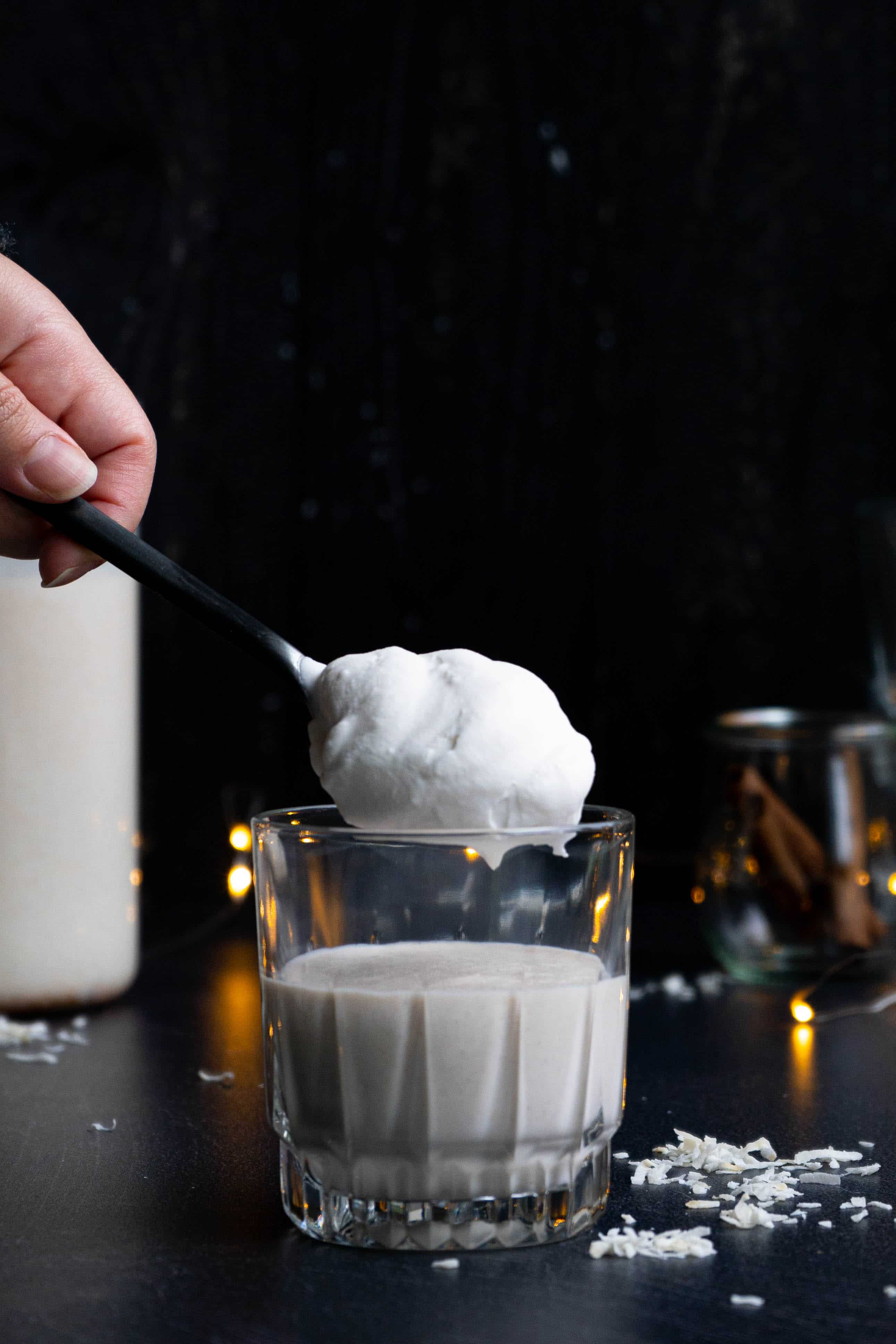 A glass of vegan coquito with a spoon full of whipped cream