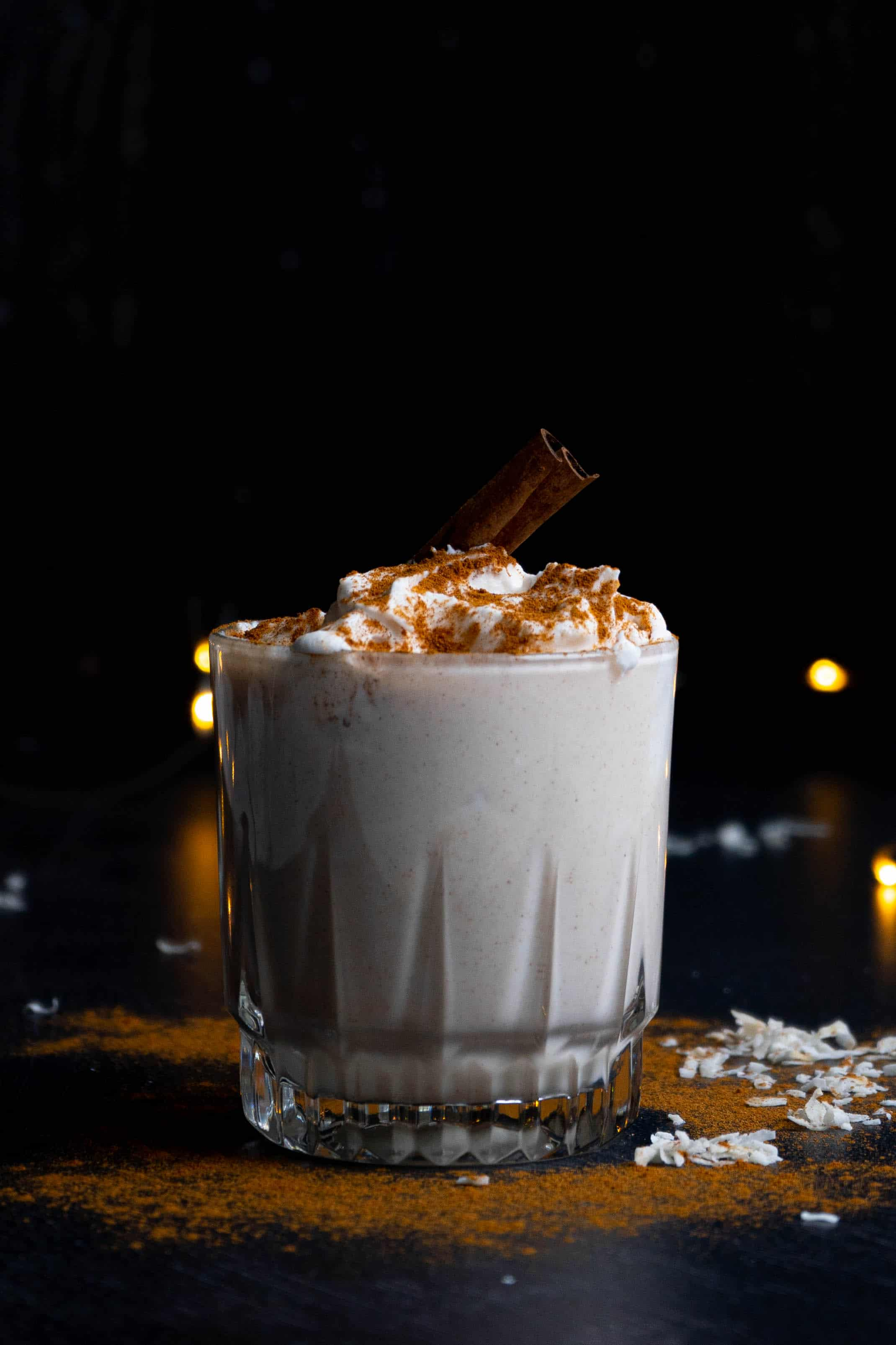 A glass of coquito with whipped cream and cinnamon