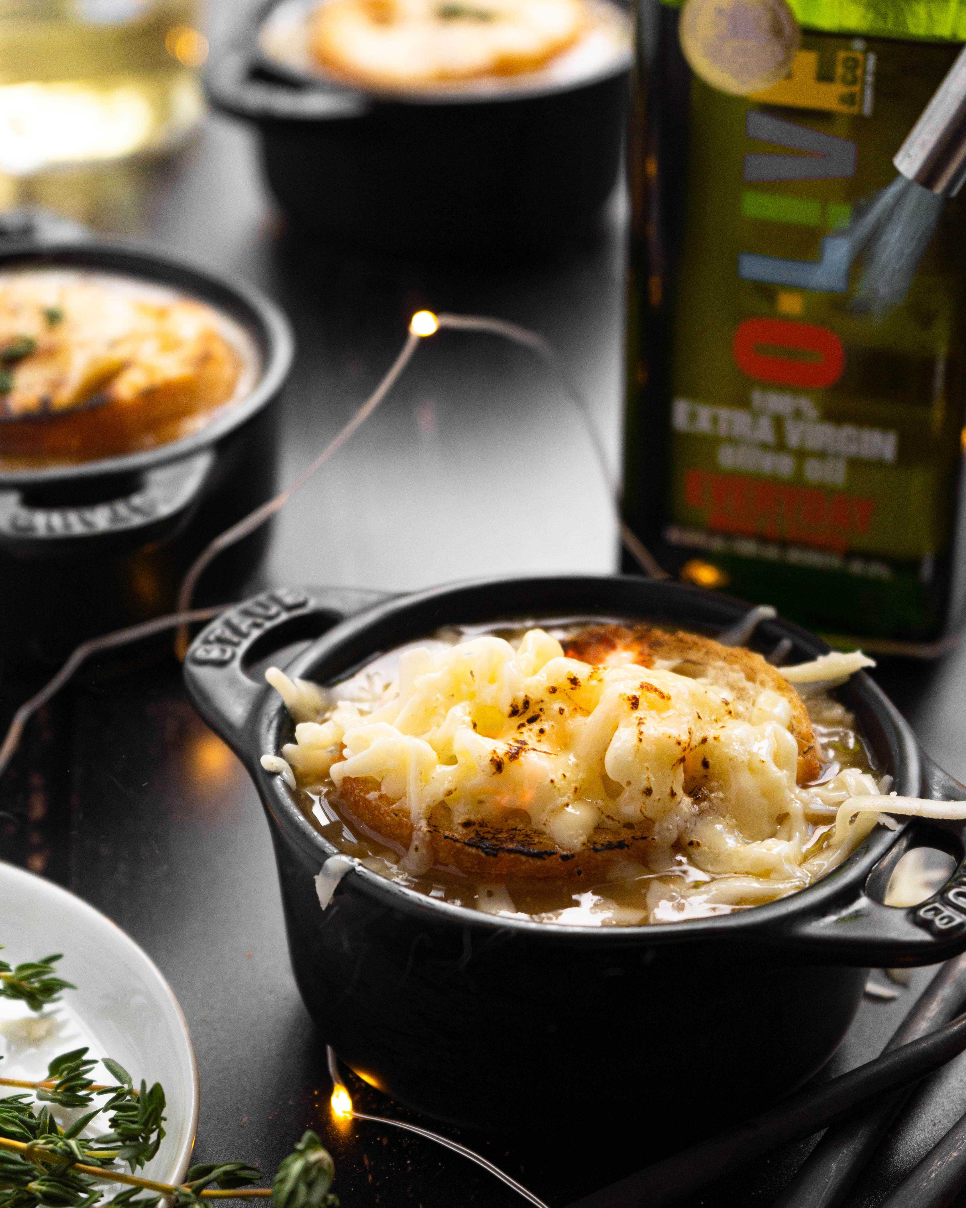 A torch melting cheese over a bowl of French Onion Soup