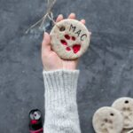 A hand holding a paw print ornament