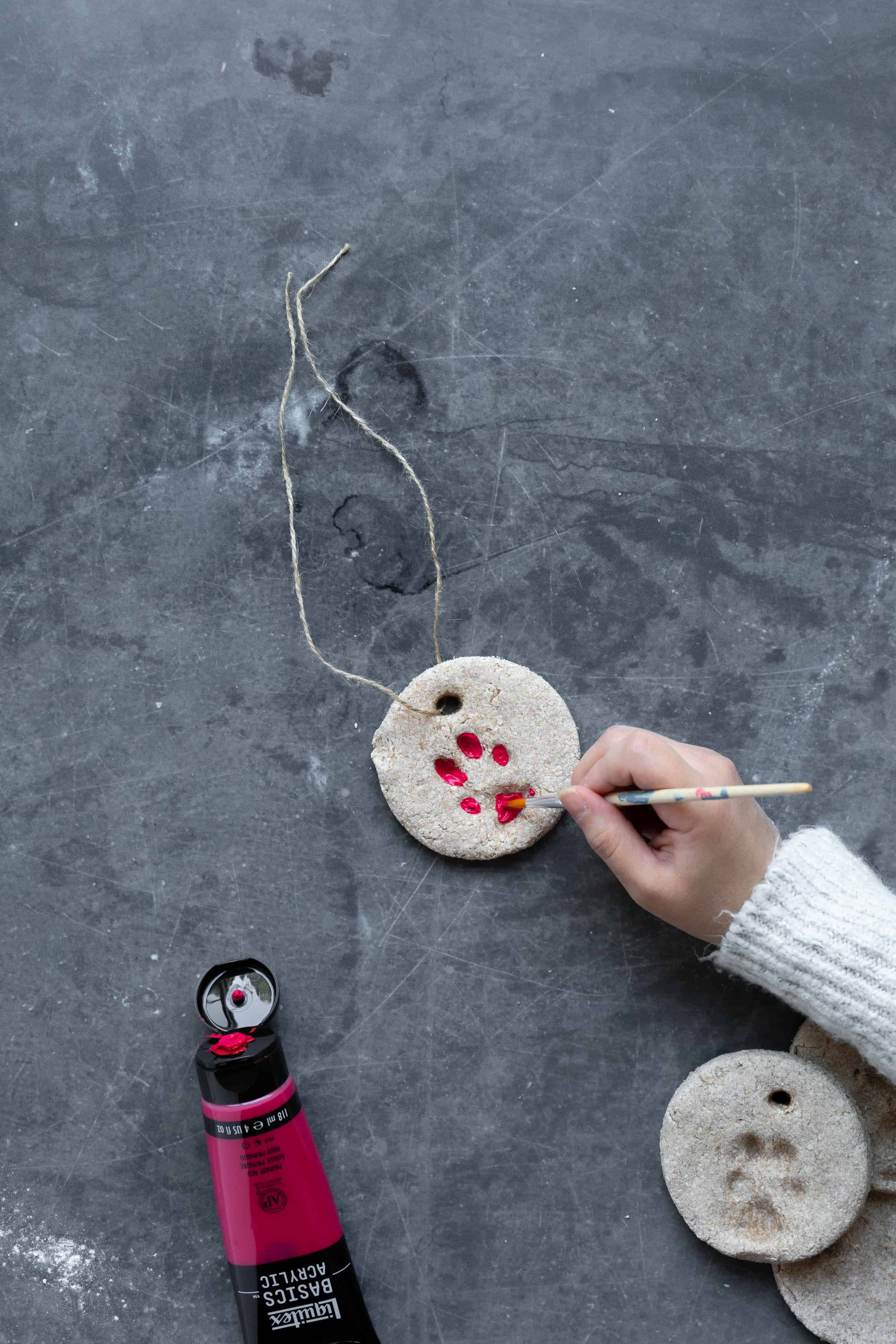 A hand painting a paw print on an ornament