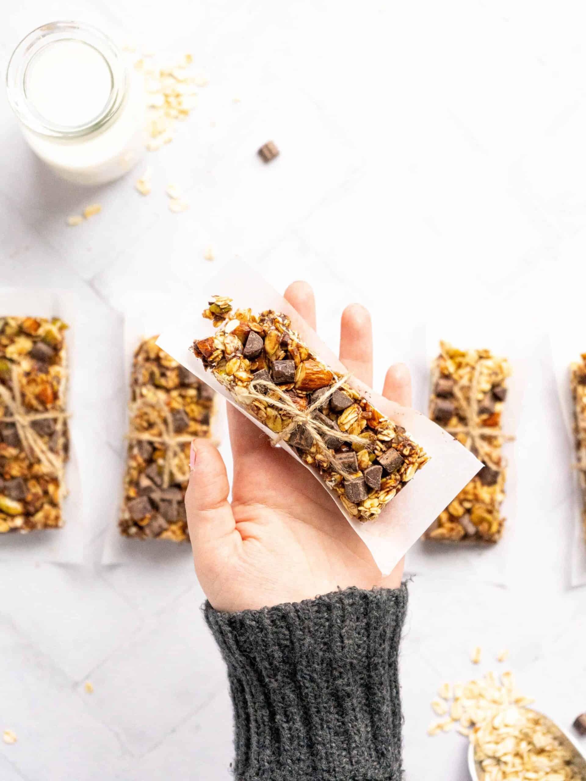 A hand holding a gluten free granola bar