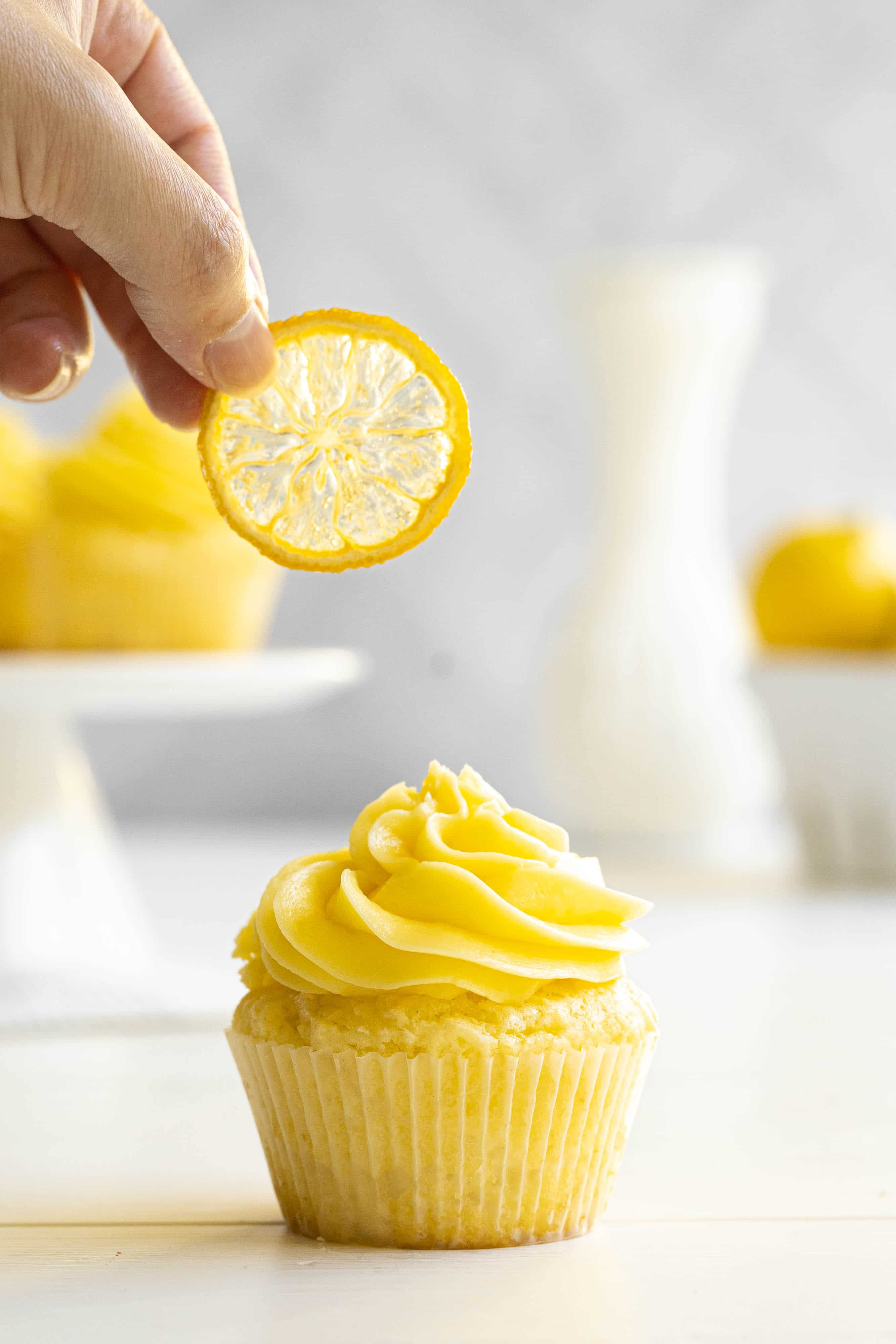 A hand placing a candied lemon slice on a cupcake