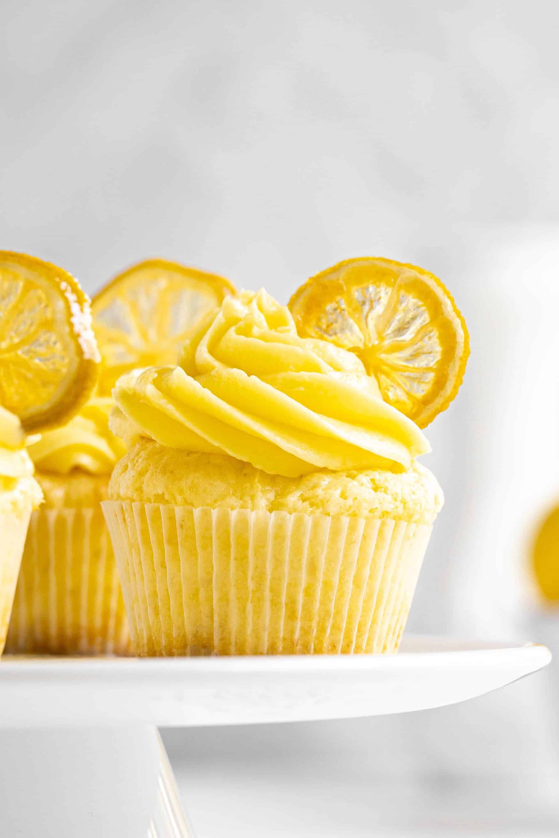 A white table with lemon cupcakes with candied lemon slices