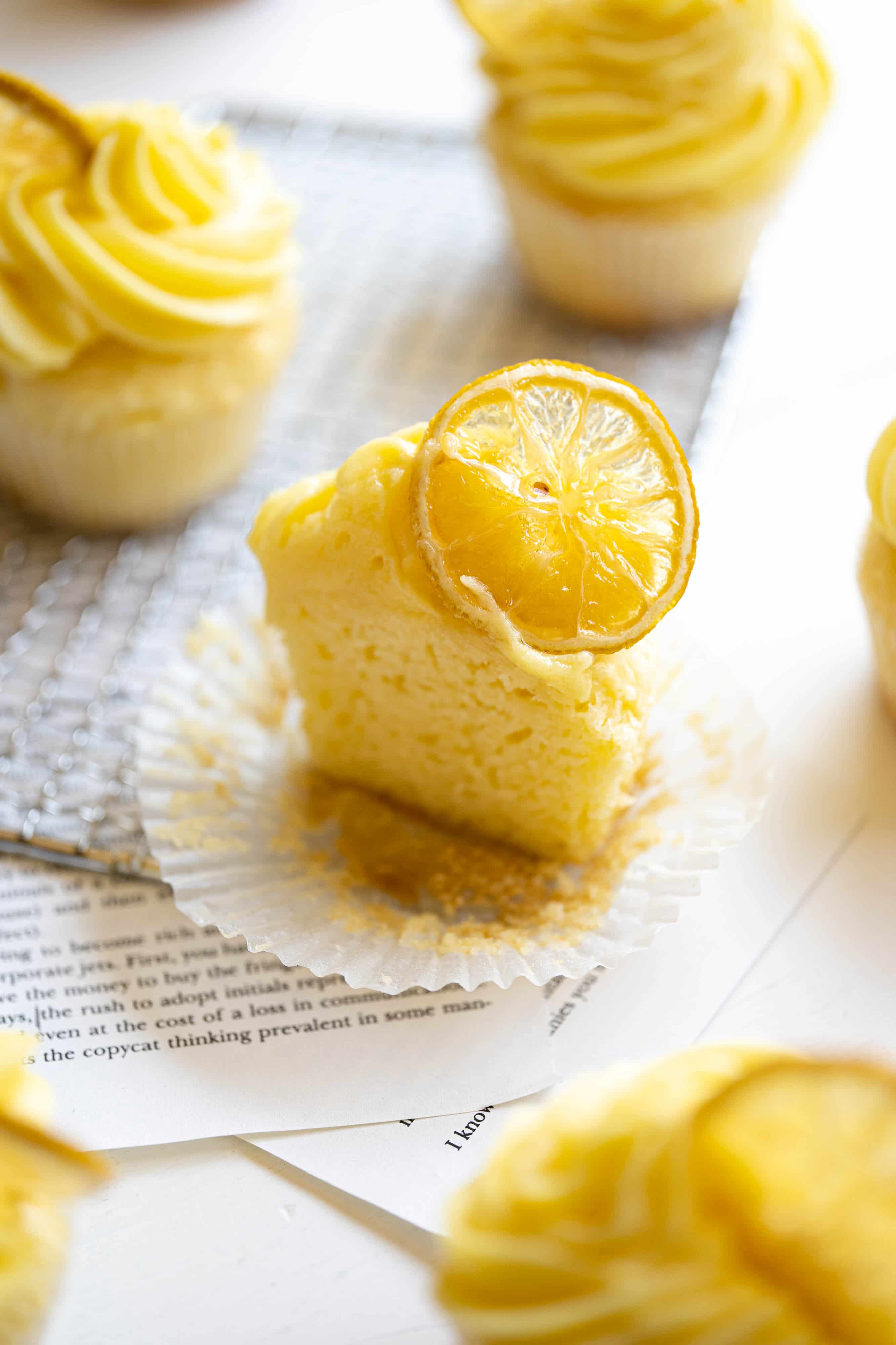 A lemon cupcake cut in half with candied lemon slices