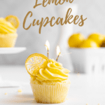 A white table with lemon cupcakes with candied lemon slices and candles