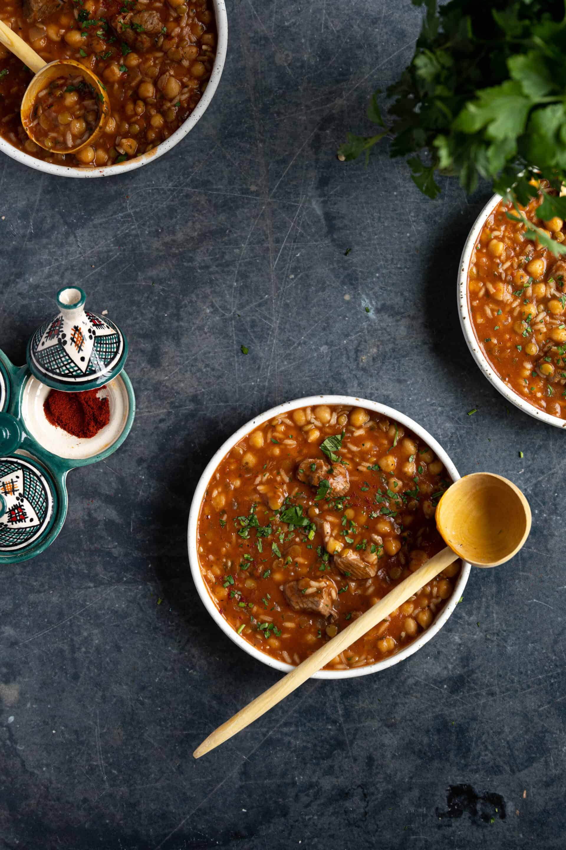 Three bowls of Moroccan soup on a black table