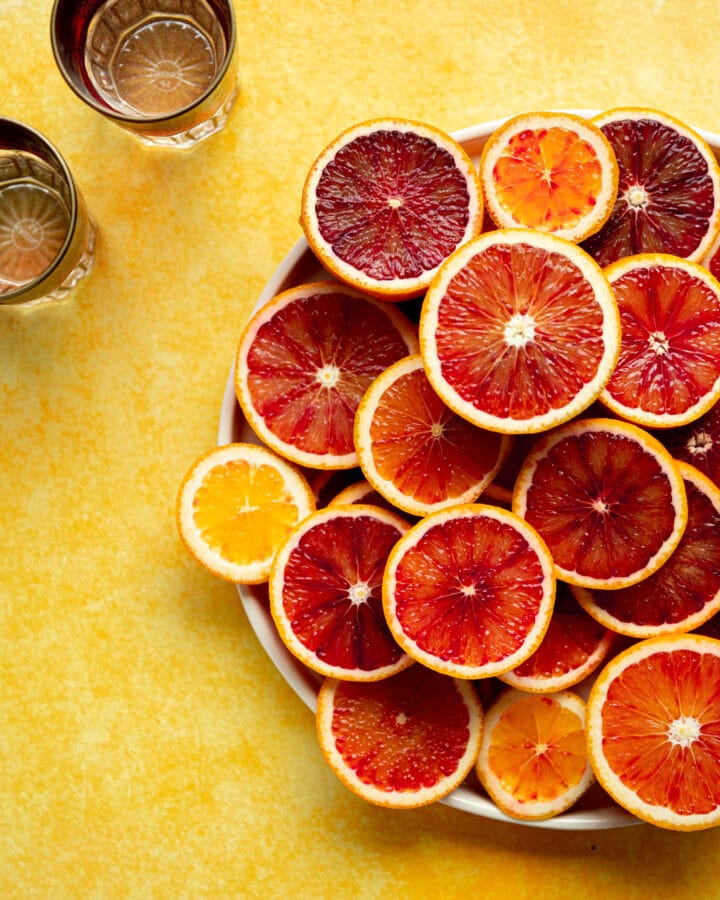 Blood orange slices on a yellow background