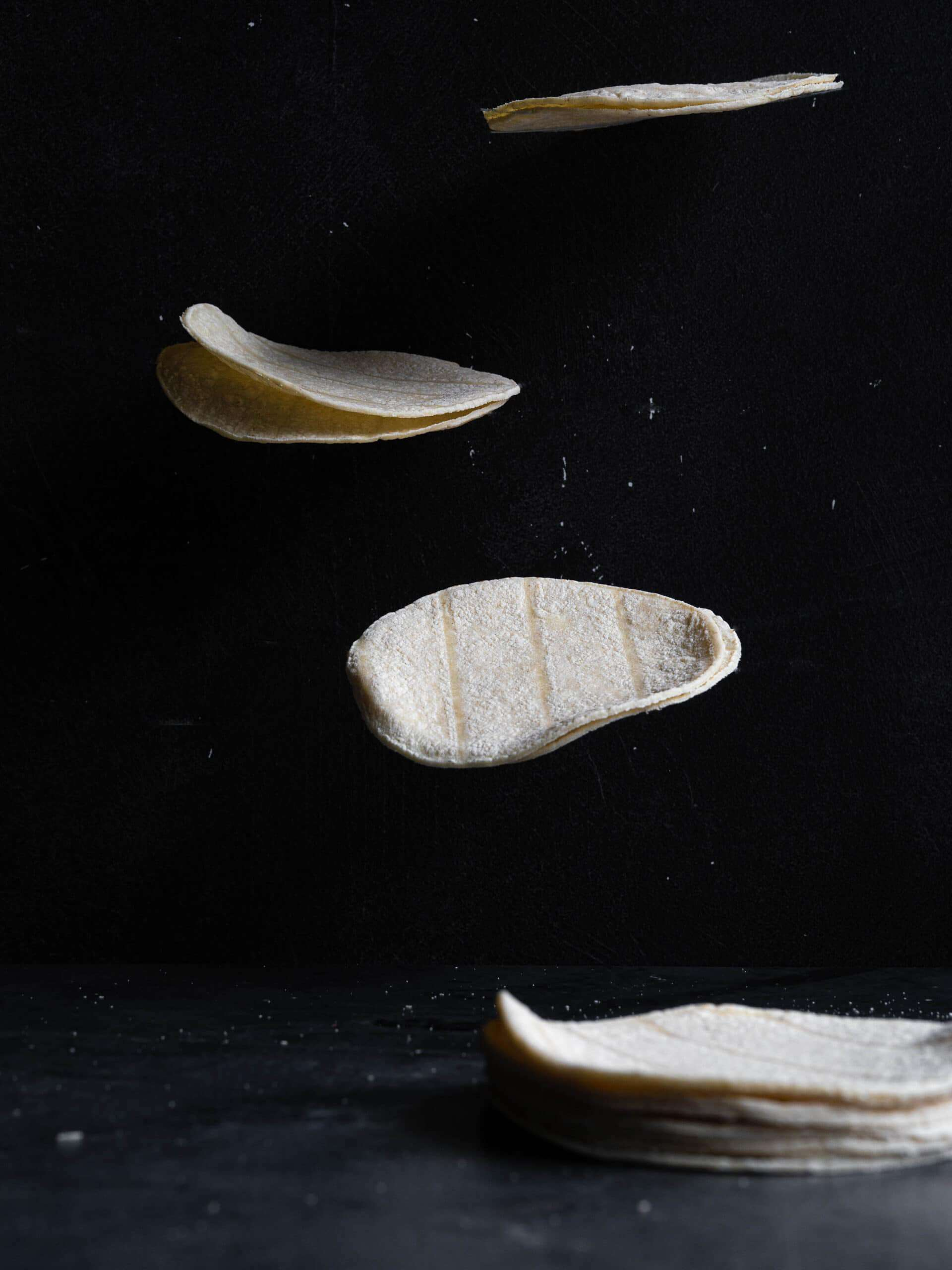 tortillas floating on a black background