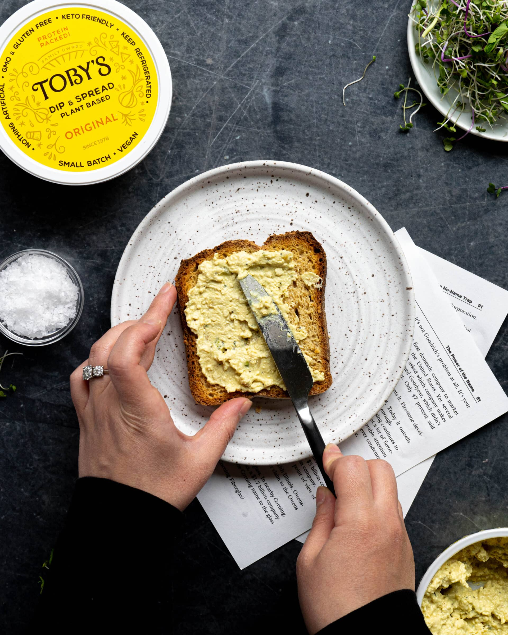 Two hands spreading spread onto toast