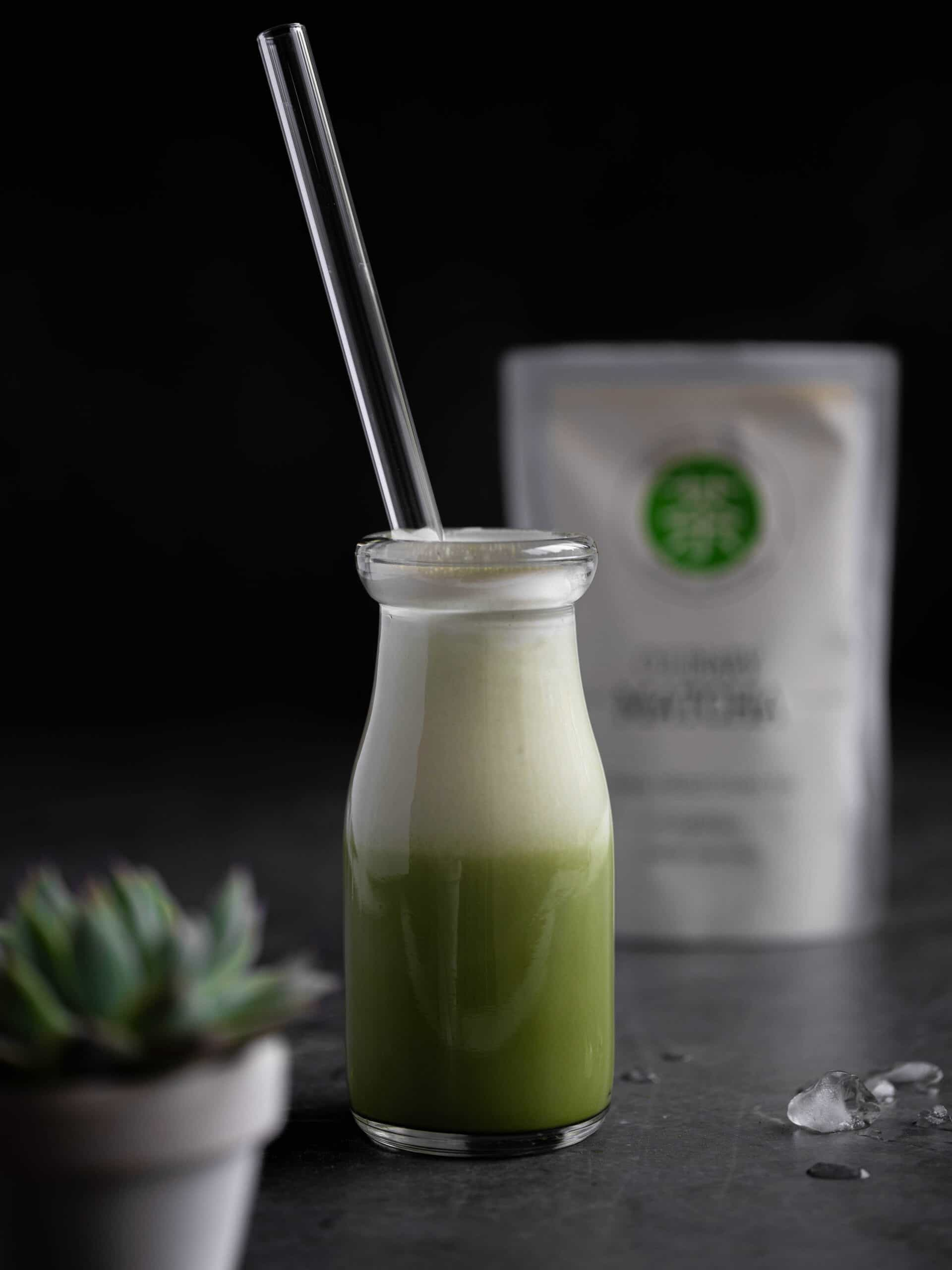 A matcha latte with a straw