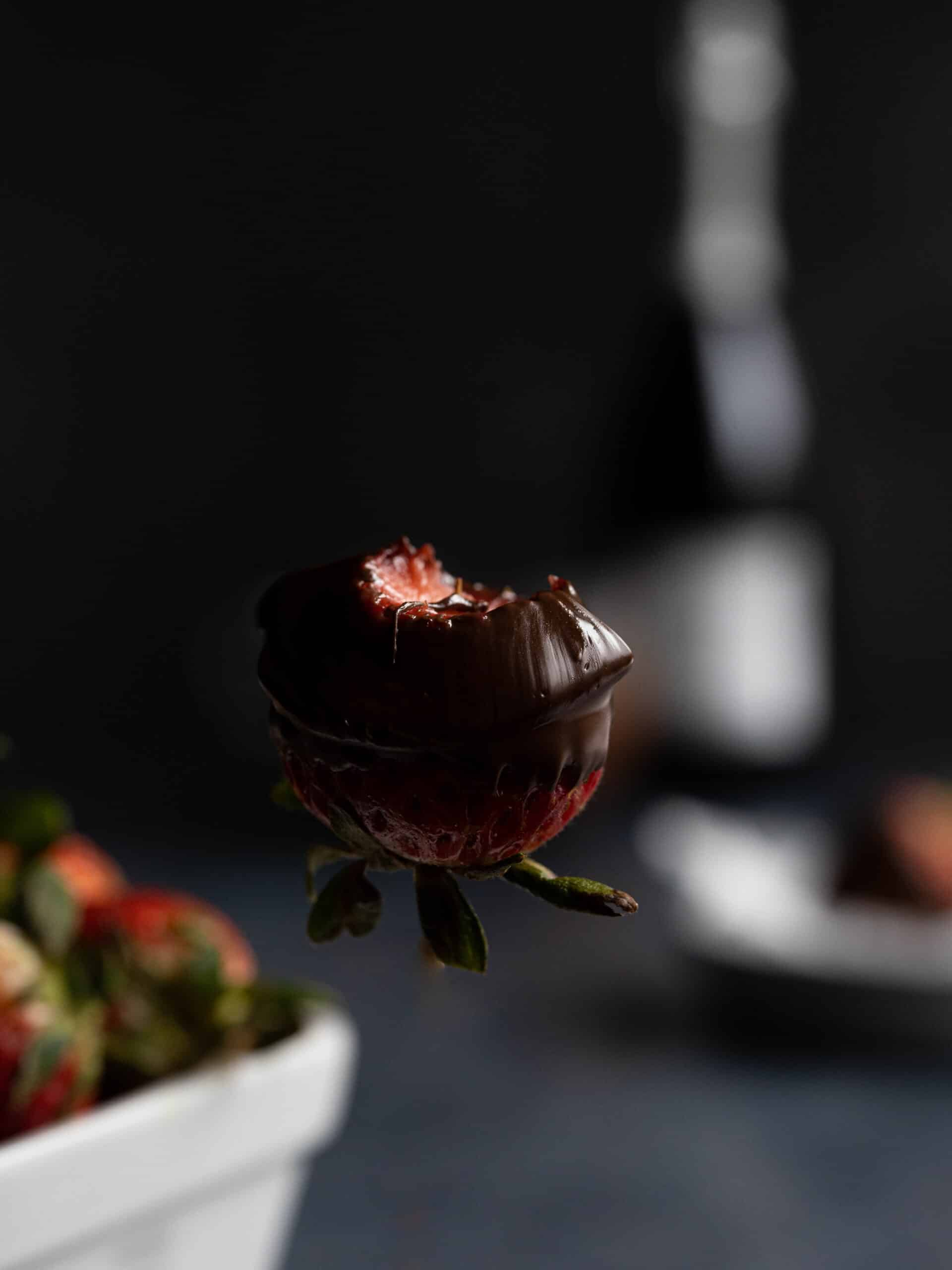 A chocolate dipped strawberry floating mid air
