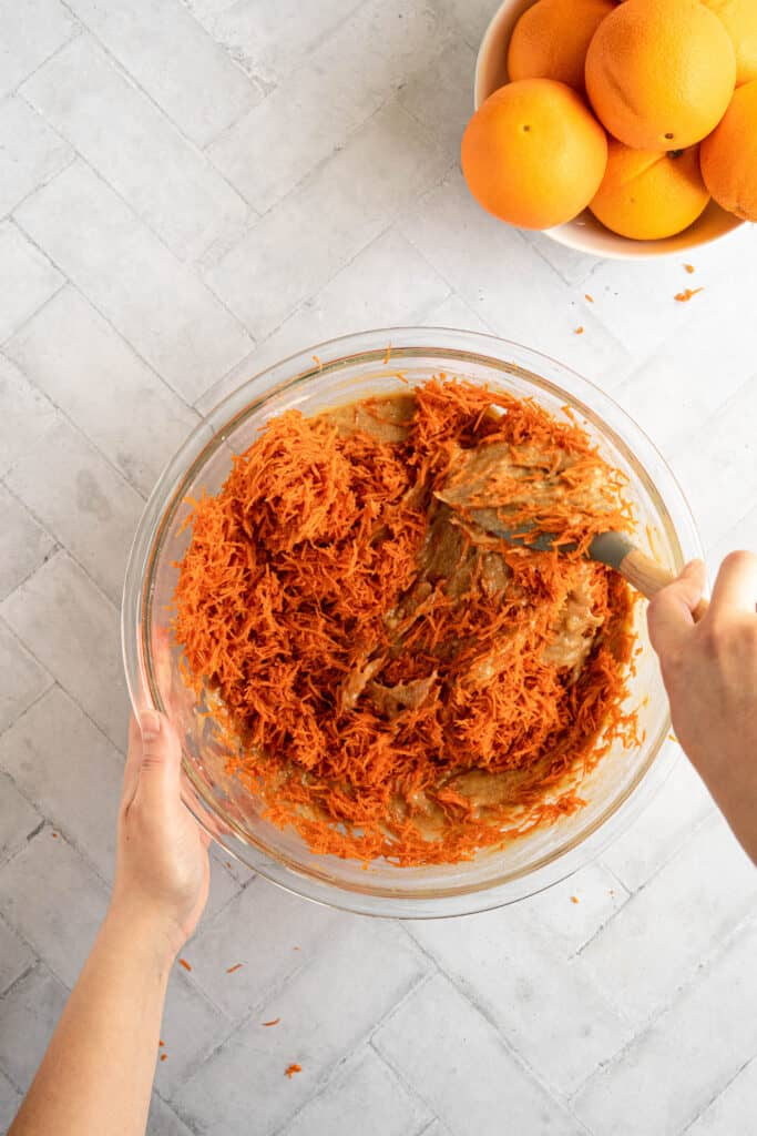 A hand folding shredded carrots into a bowl of batter