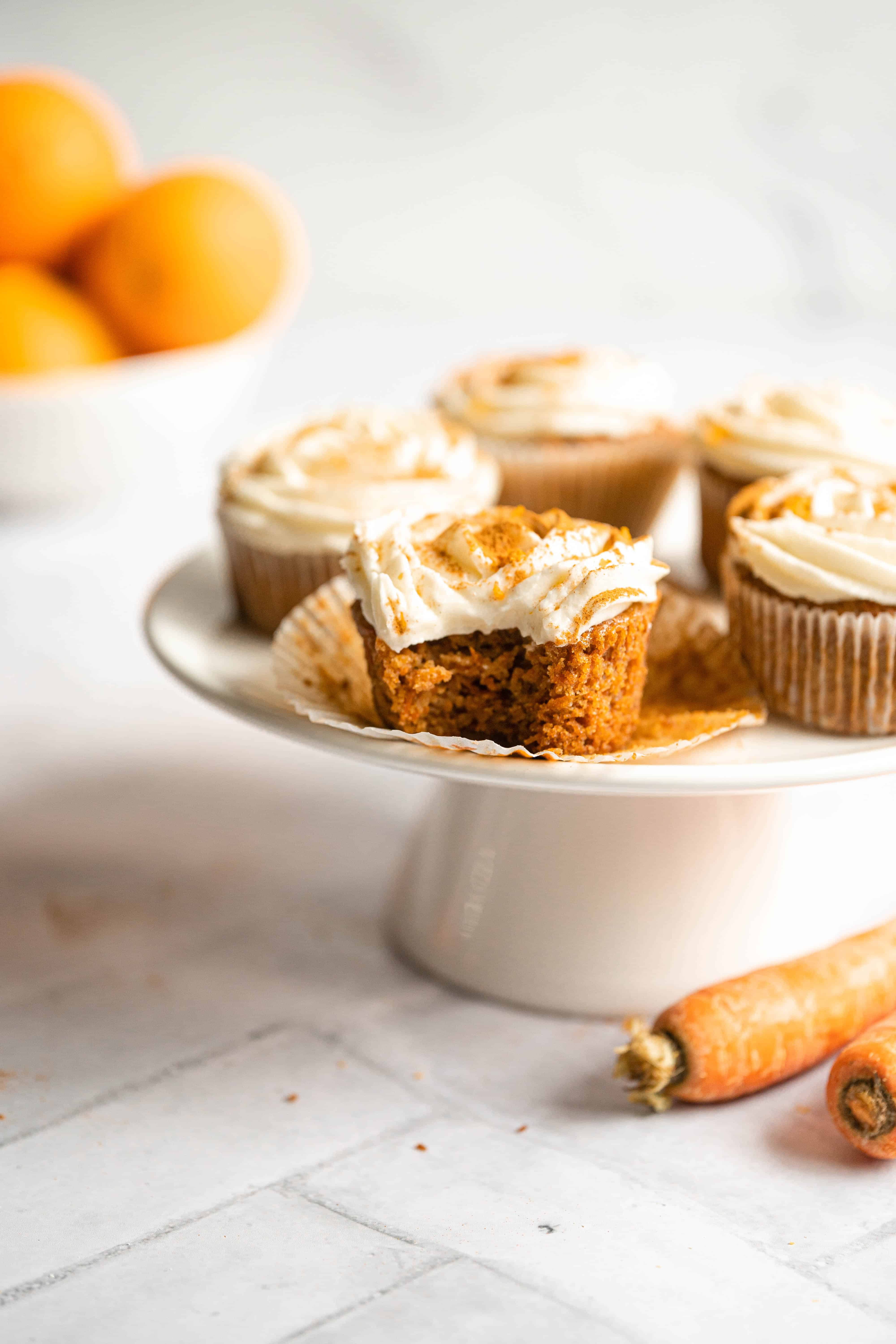 A bite taken out of a carrot cupcake with orange cream cheese frosting