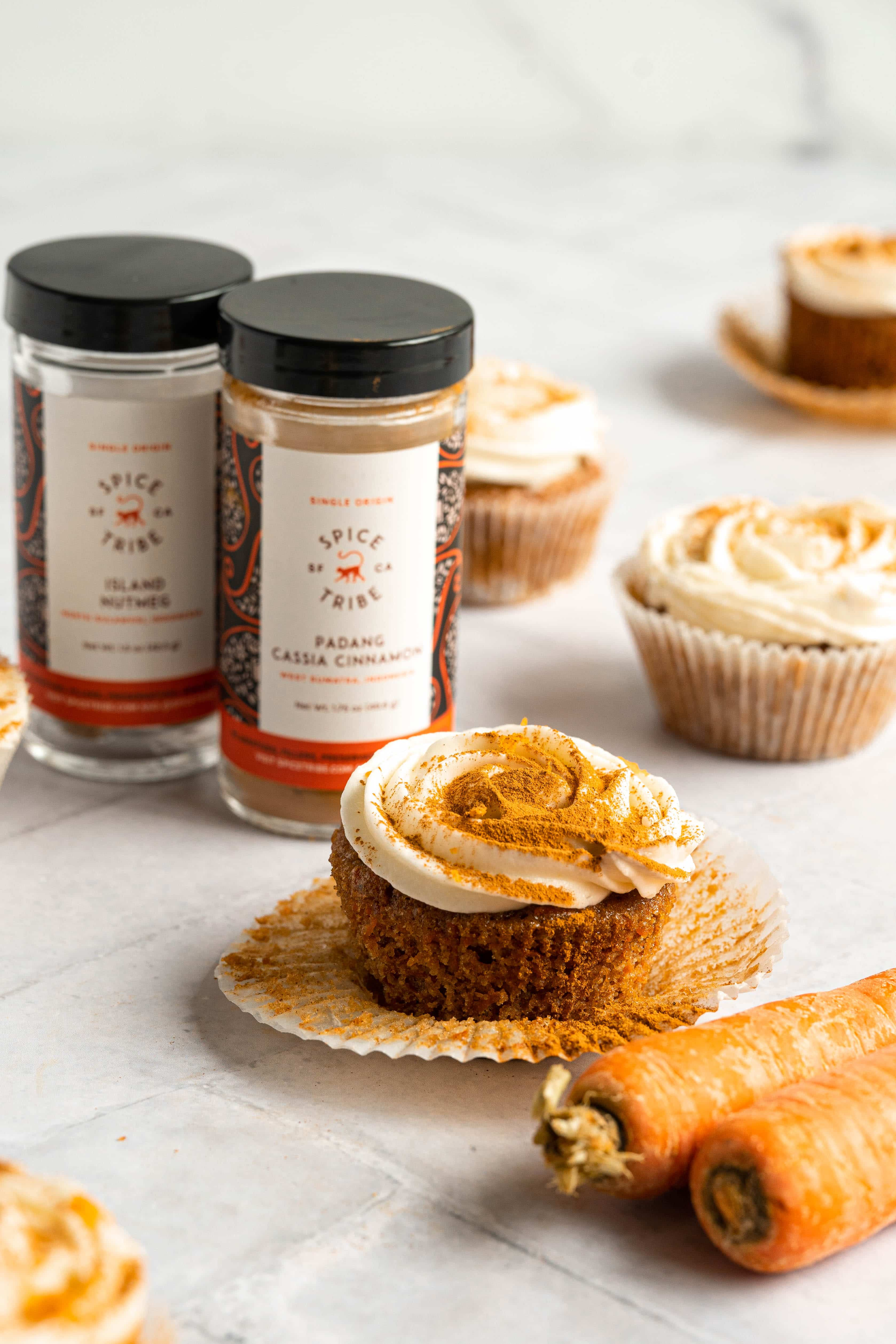 A carrot cupcake next to carrots and spices