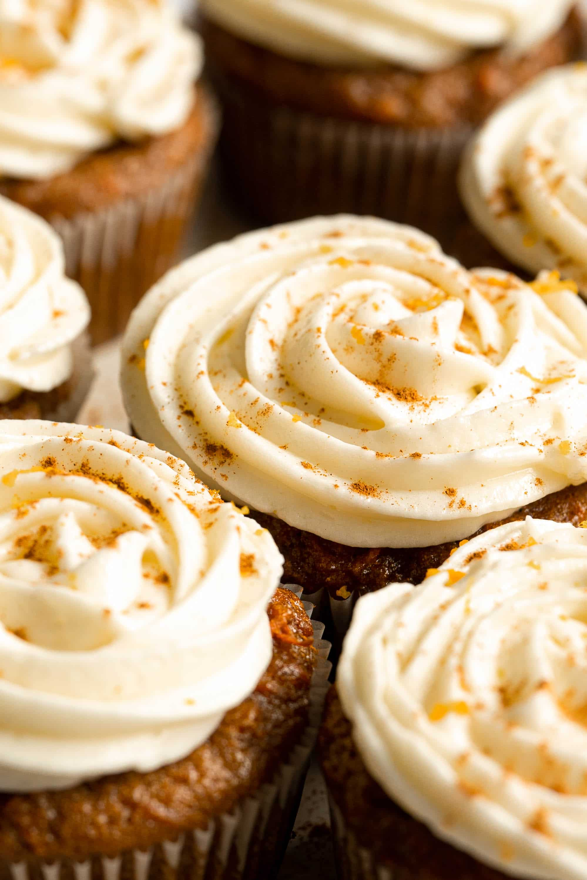 A close up of orange cream cheese frosting on cupcakes