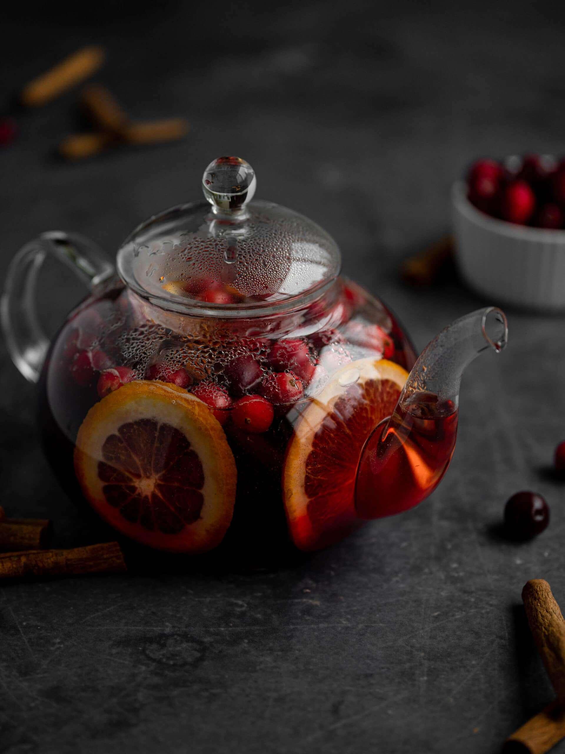 A citrus cranberry tea in a glass teapot