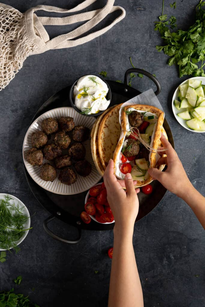 hands reaching in to grab a pita
