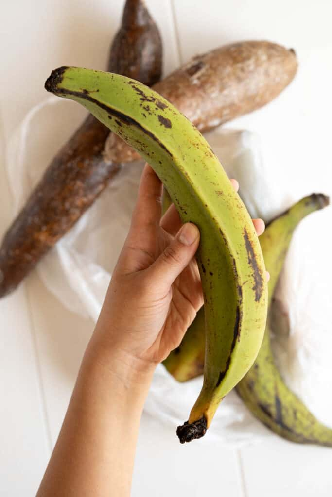 a hand holding a green plantain