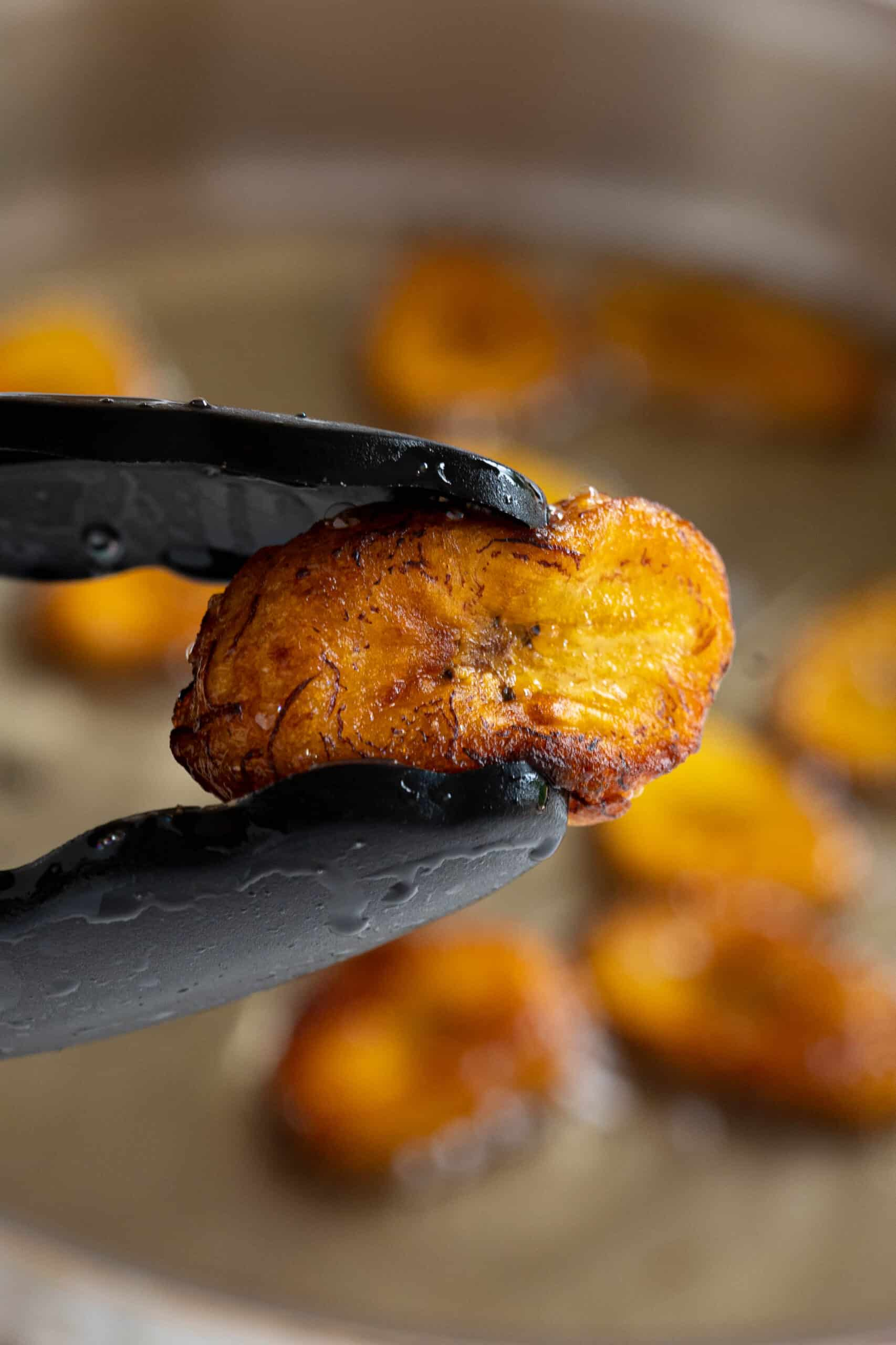 tongs holding a sweet fried plantain
