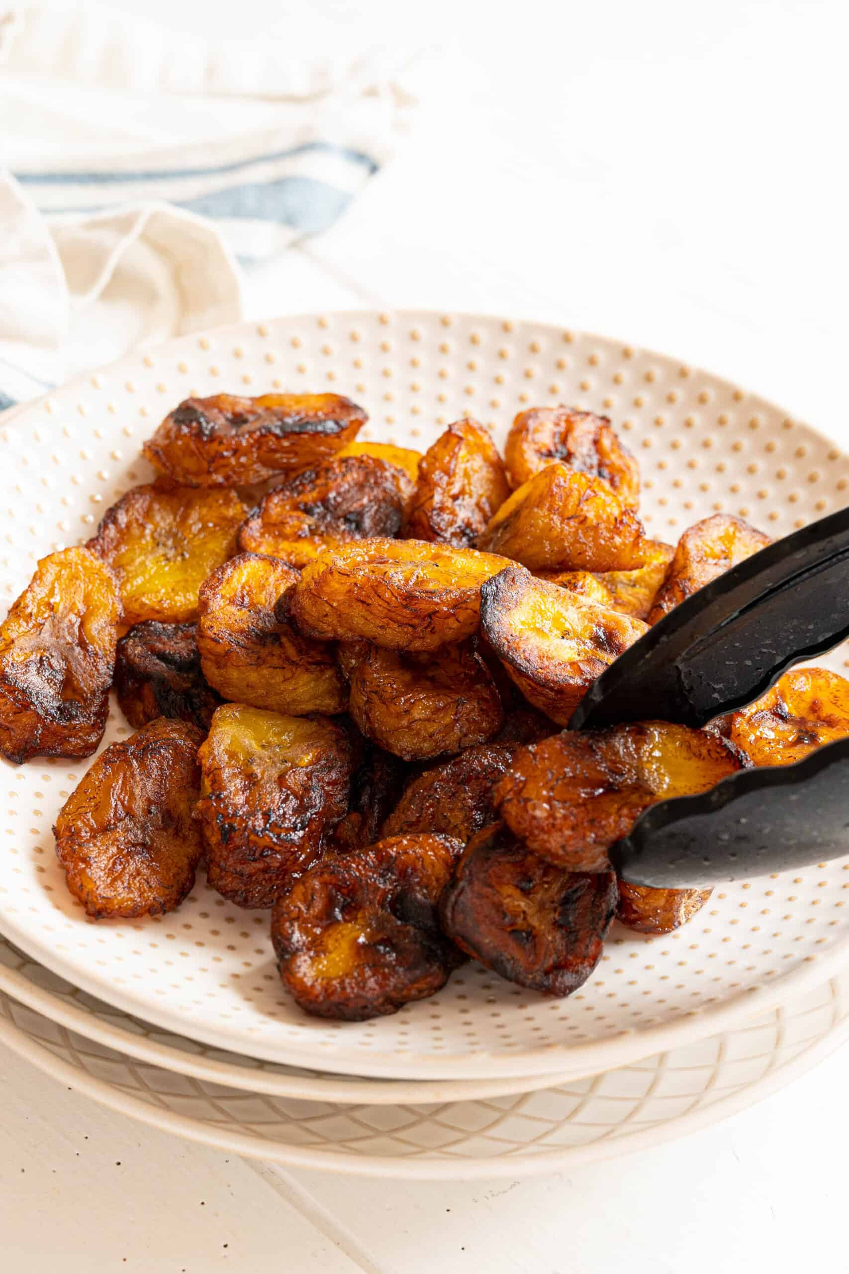 tongs placing a fried plantain on a plate