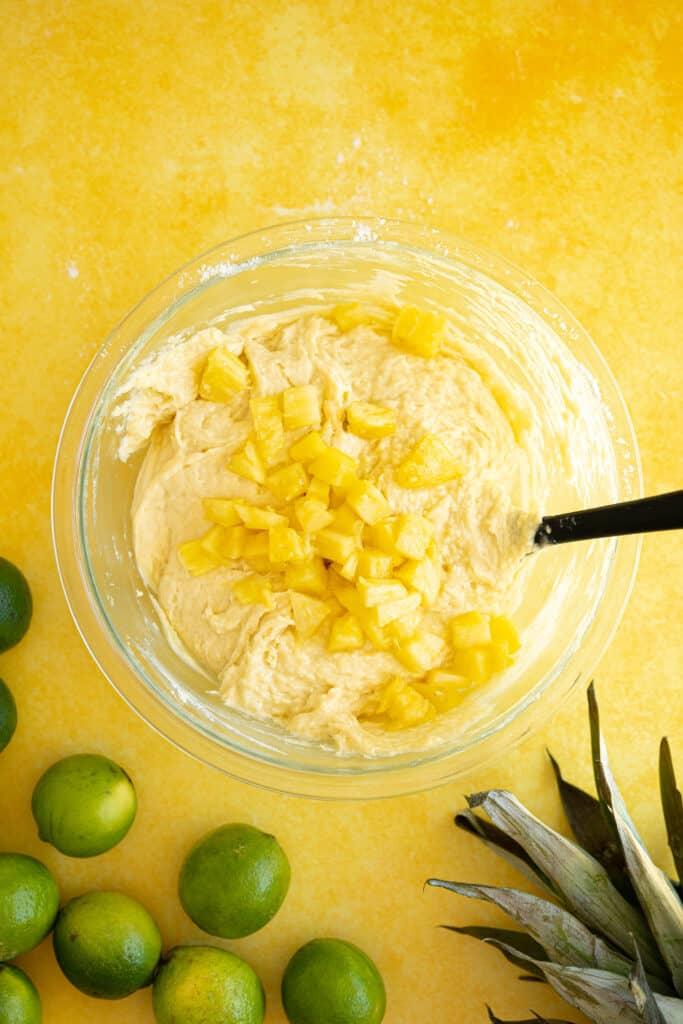 pineapple chunks in a bowl of cake batter